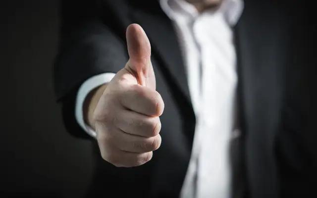 Un hombre mostrando una mano con pulgar arriba