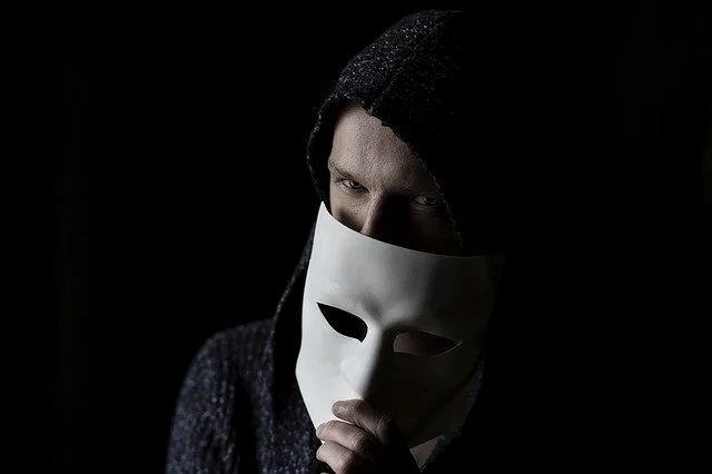 Hombre vestido de negro quitándose una máscara del rostro