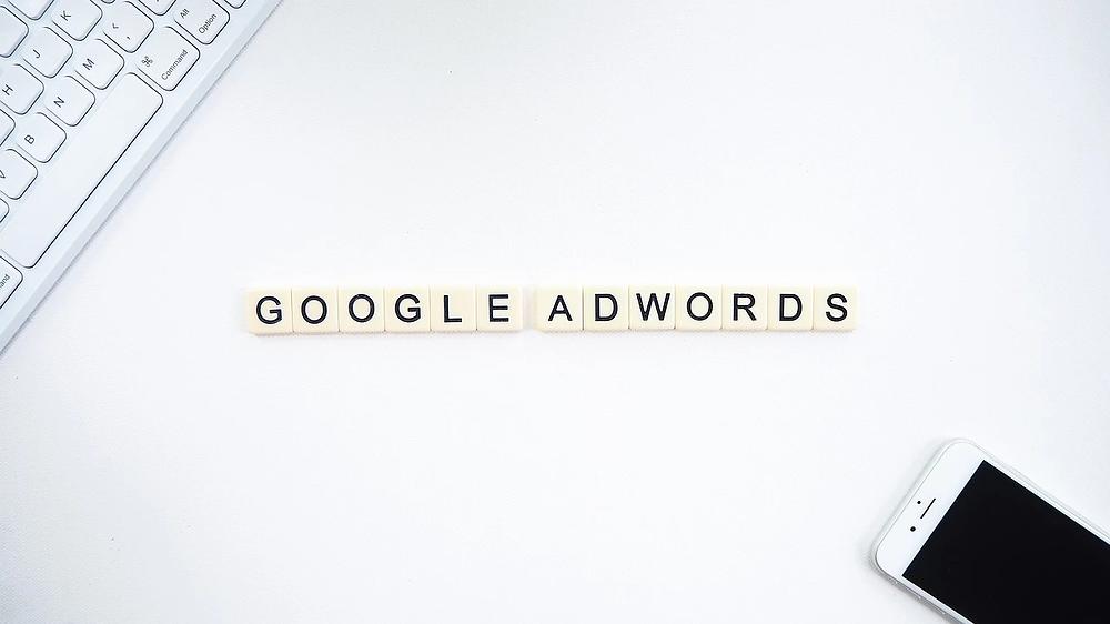 """Piezas de Scrabble formando la palabra """"Google Adwords"""" en un escritorio blanco junto a un teclado y un smartphone"""