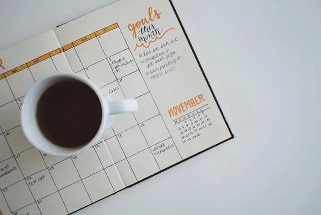 Una taza de café sobre una agenda