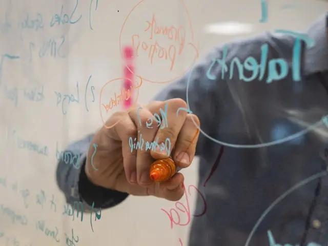 Persona escribiendo en pizarra transparente