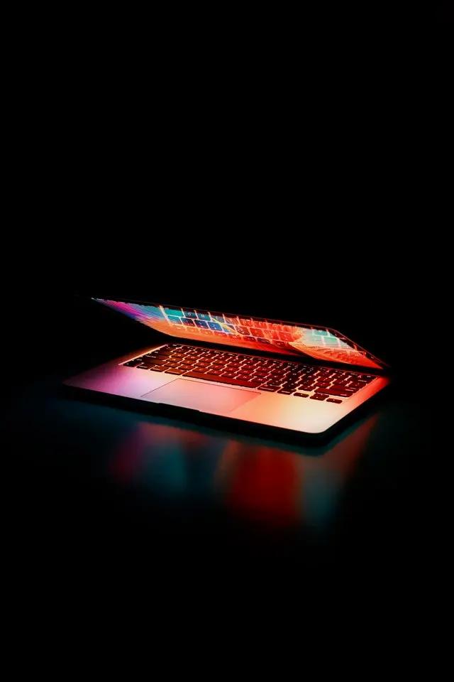 Una laptop semiabierta en un fondo negro