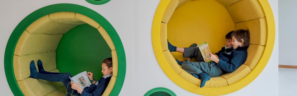 Niños sentados dentro de círculos acolchonados en el interior de una pared