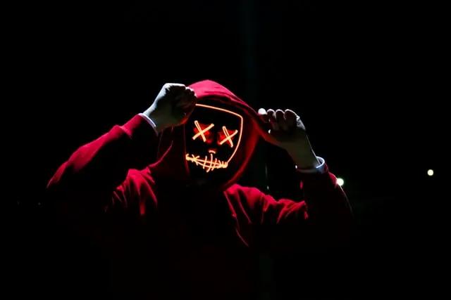 Joven vestido con hodie rojo y portando una máscara luminosa