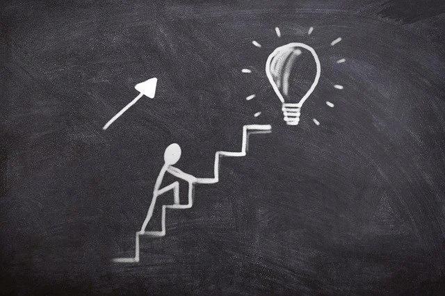 El dibujo en tiza de un hombre subiendo una escalera en cuya cima hay un foco encendido