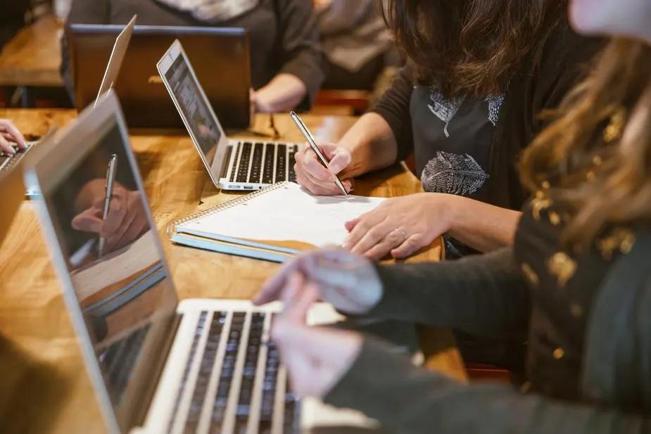 Chicas tomando apuntes junto a sus laptops