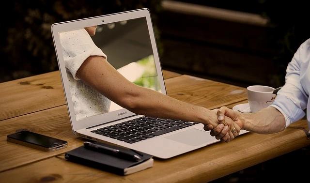 Un brazo sale de la pantalla de una laptop y le da un apretón de manos a la persona está del otro lado