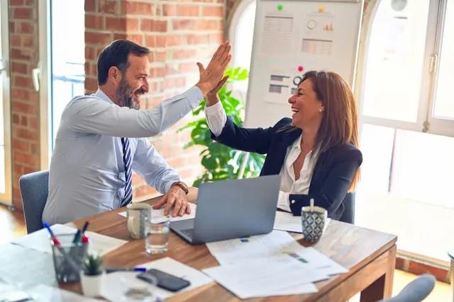 Dos empleados felices chocan sus manos durante una junta de trabajo