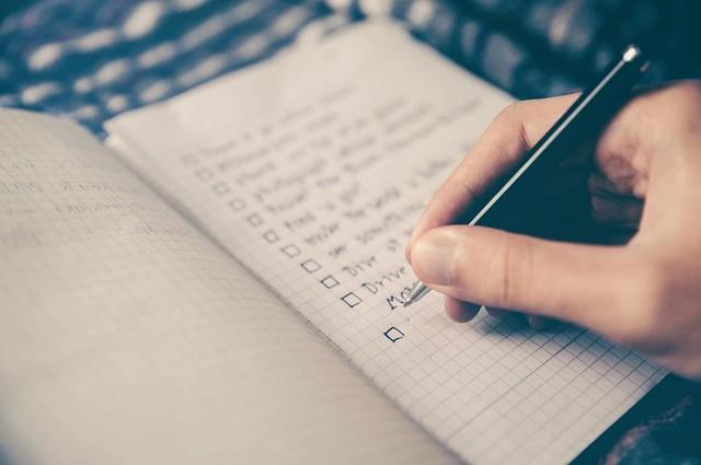 Una mano llenando una lista de tareas en una libreta