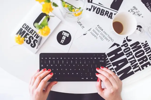 Unas manos escribiendo sobre un teclado rodeado de papeles