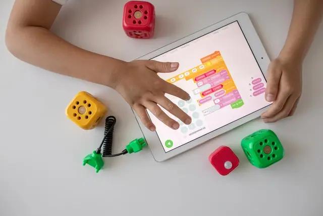 Niño jugando con una tablet y cubos de colores