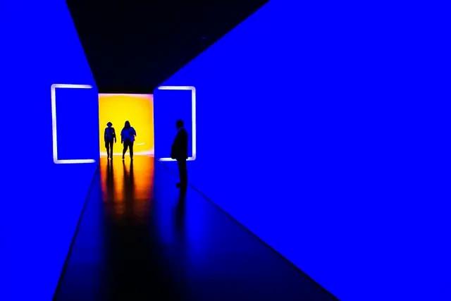 Tres personas caminando por un pasillo con paredes azules