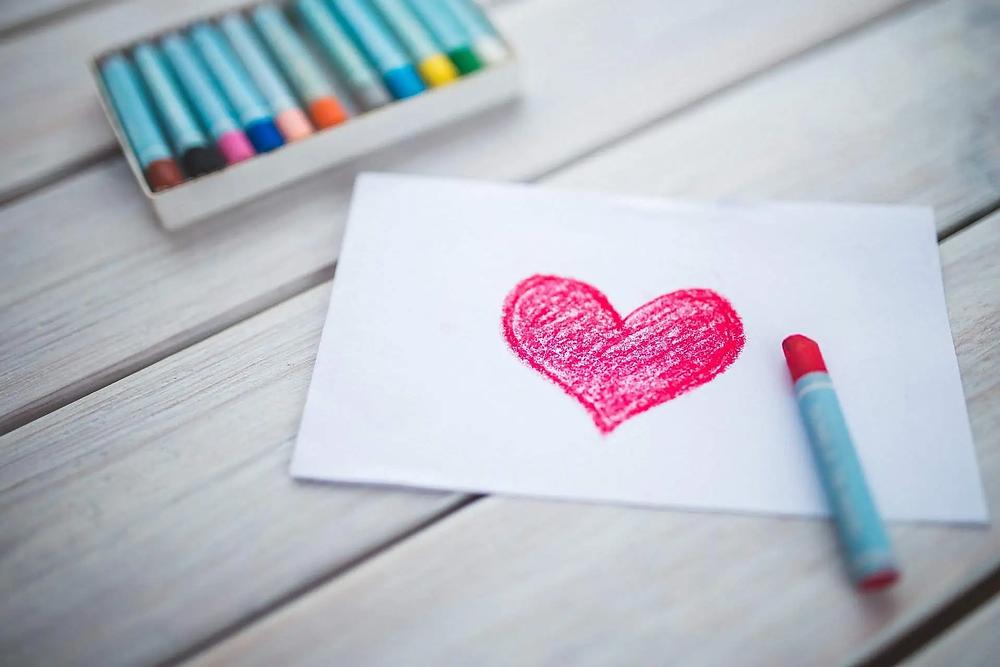 En una mesa vemos unos collores y una hoja con un corazón dibujado