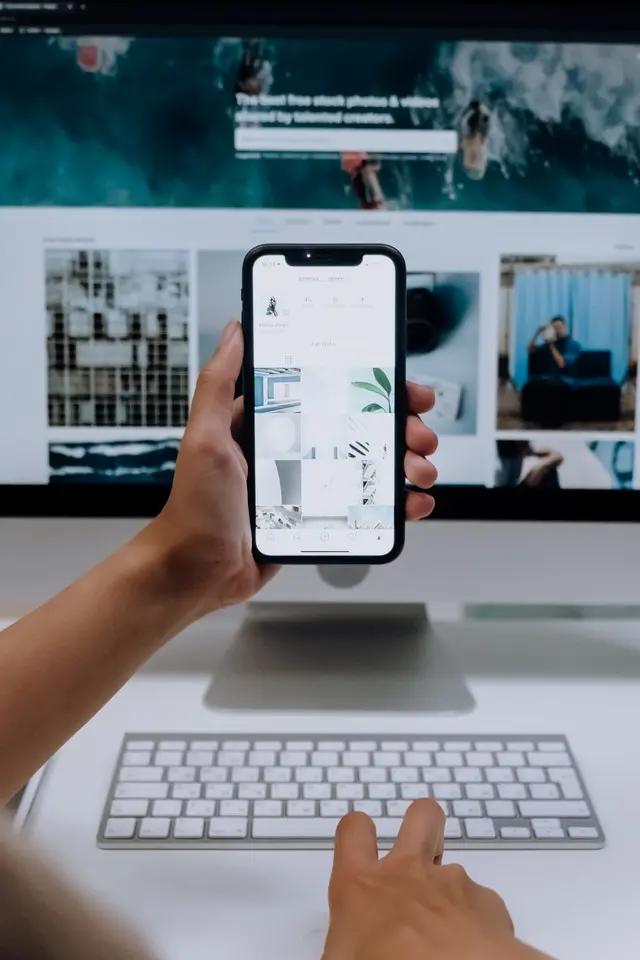 Una mano sostiene un smartphone frente a una computadora MAC