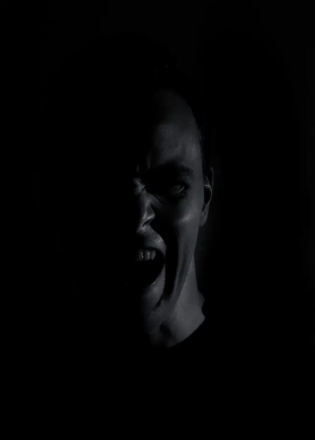 Hombre gritando en fondo negro