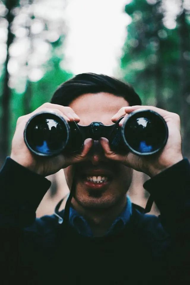 Hombre mirando a la cámara por unos binoculares