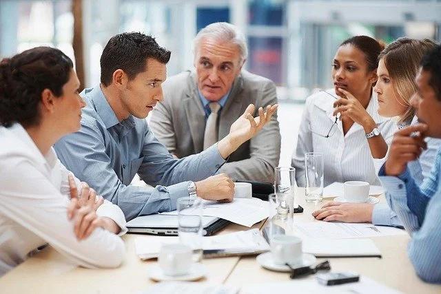 6 personas sentadas en una mesa, uno de ellos habla y los demás lo escuchan con interés.