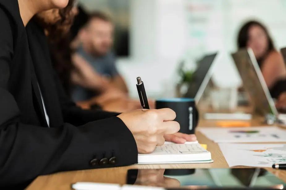 Persona escribiendo en una junta de trabajo