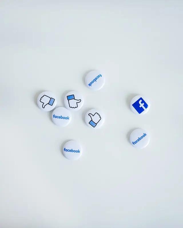 """Unos pins con el logotipo de Facebook y el ícono de """"Like"""""""