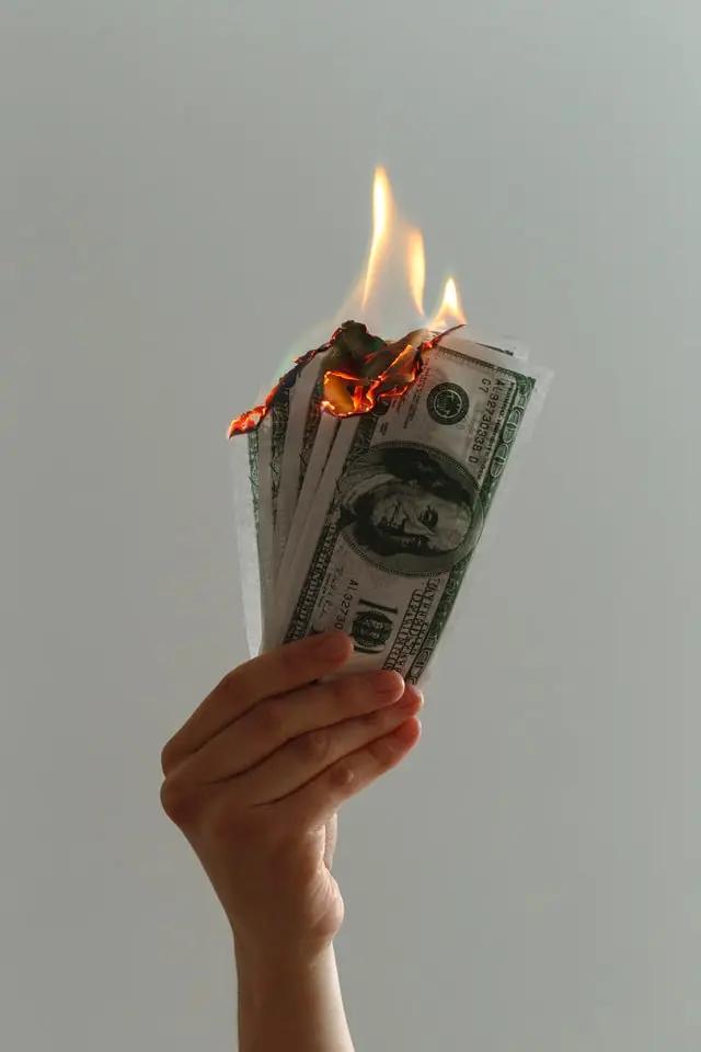 Una mano sostiene dólares quemándose