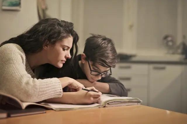 Mujer ayuda a su hijo a hacer la tarea