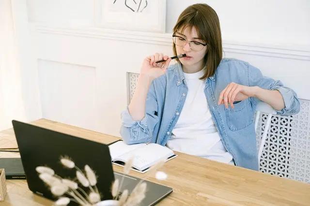 Mujer frente a una laptop pensando sobre qué escribir