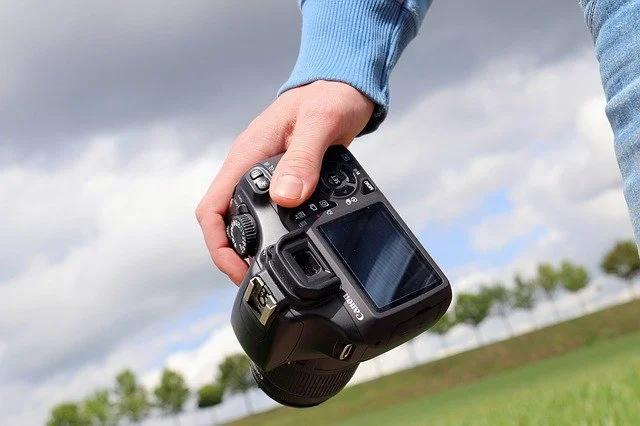 Una mano sosteniendo una cámara fotográfica