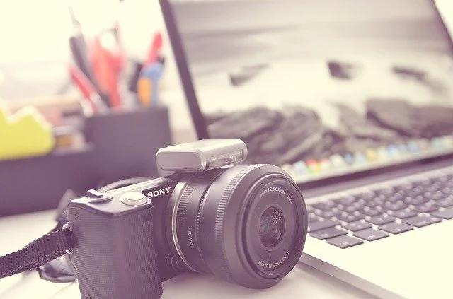 Una cámara fotográfica junto a una laptop