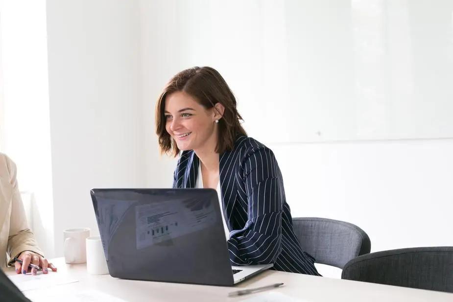 Mujer sonriente sentada frente a una laptop