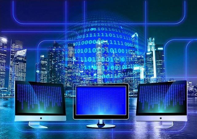 3 computadorascon códigos binarios en sus pantallas, al fondo se ve una ciudad con edificios