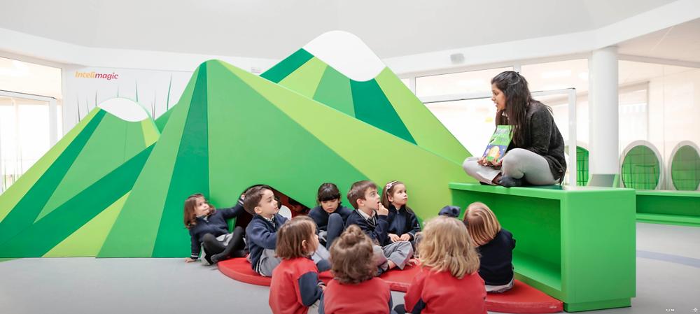 Maestra impartiendo clase a niños en un aula con diseño creativo