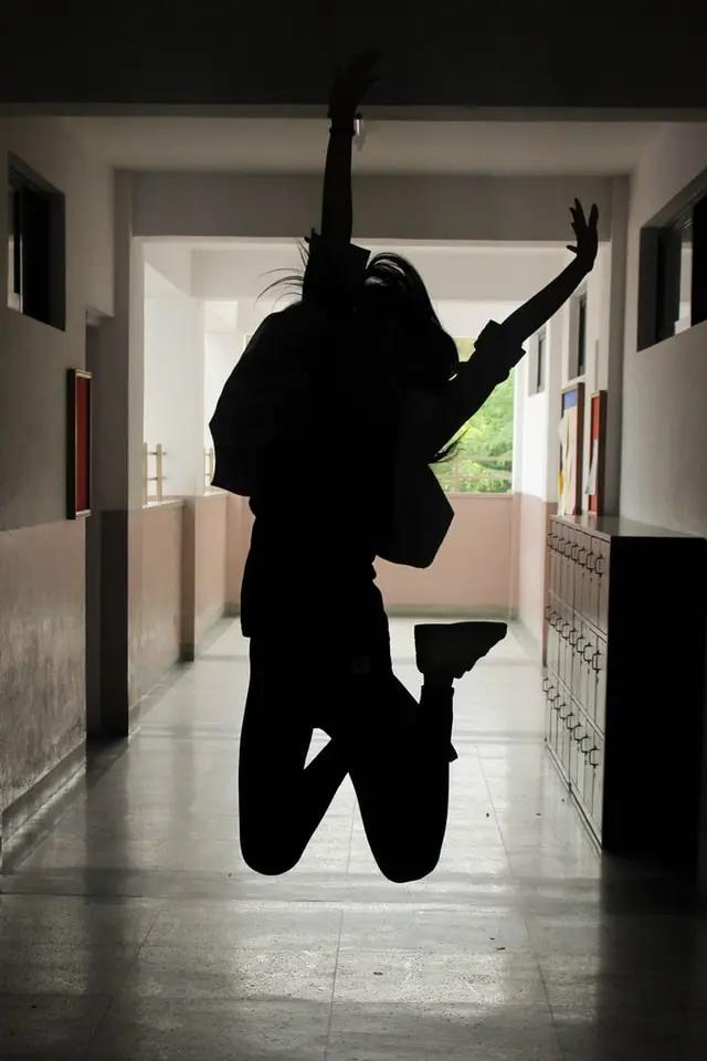 La silueta de una chica saltando en un pasillo