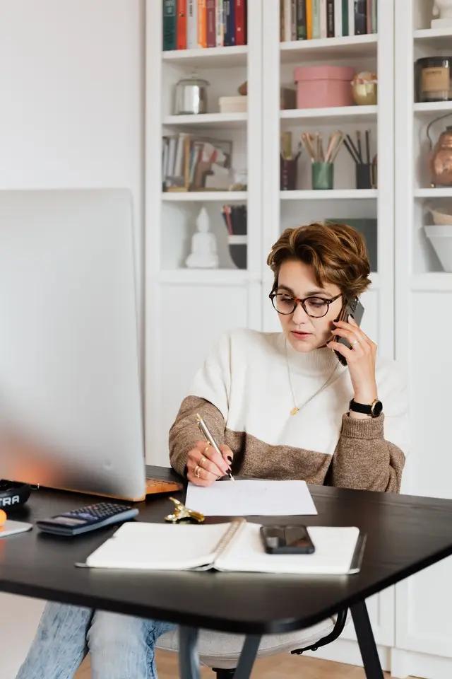 Una mujer hablando por teléfono mientras toma apuntes en su escritorio