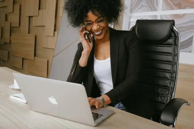 Mujer hablando por teléfono frente a una laptop