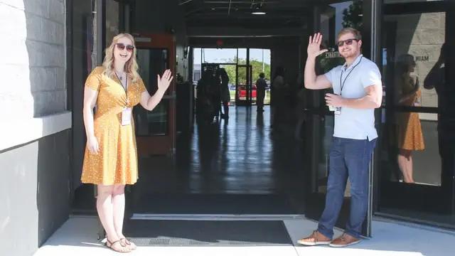 Dos personas recibiendo a alguien y saludando
