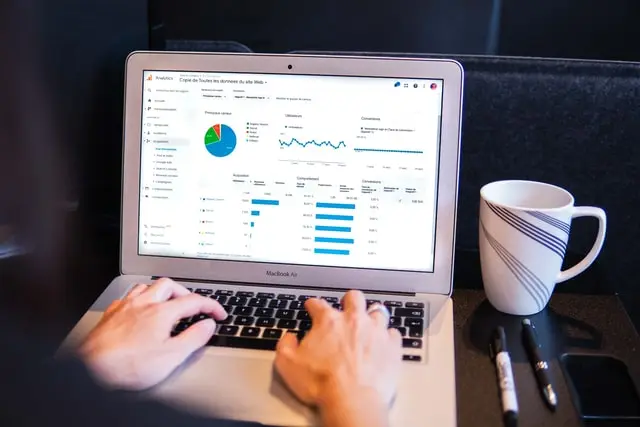 Persona escribiendo en una laptop que muestra gráficos estadísticos