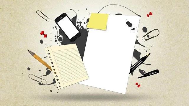 Hojas de papel en blanco, un smartphone, un lápiz, un bolígrafo y clips.
