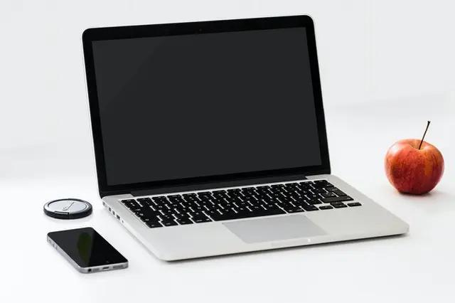 Una laptop junto a una manzana y un smartphone