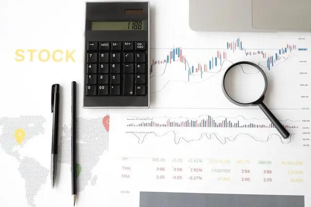 Gráficos en hojas junto a calculadora, bolígrafos y lupa