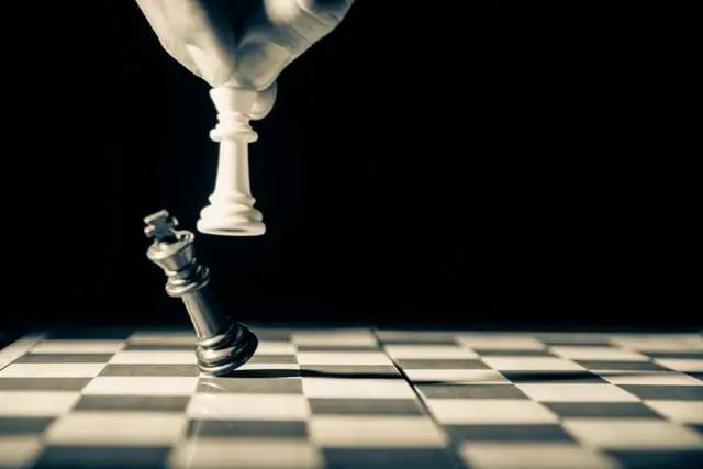 Alguien mueve una pieza en un tablero de ajedrez