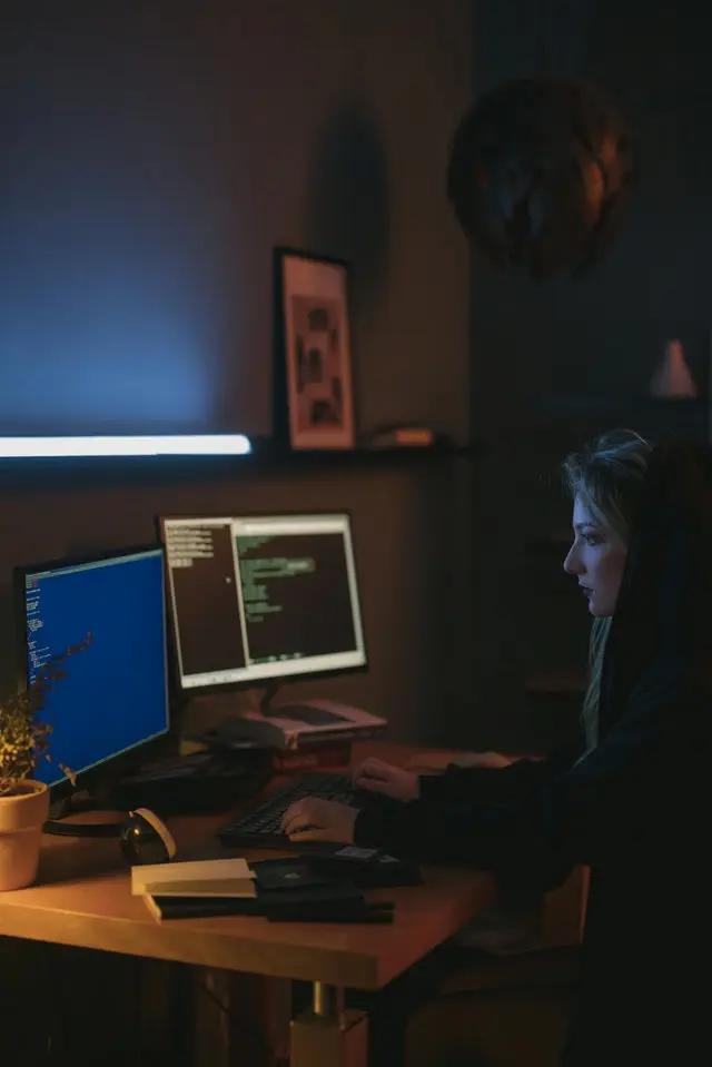 Mujer frente a dos computadoras
