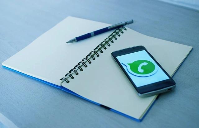 Una libreta, un bolígrafo y un smartphone con el ícono de WhatsApp