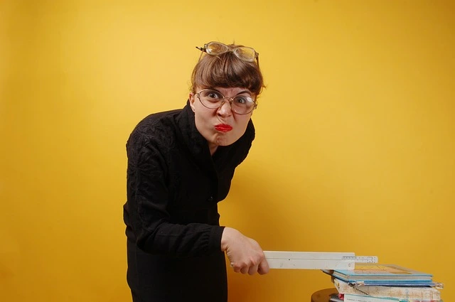 Maestra enojada golpeando unos libros con una regla