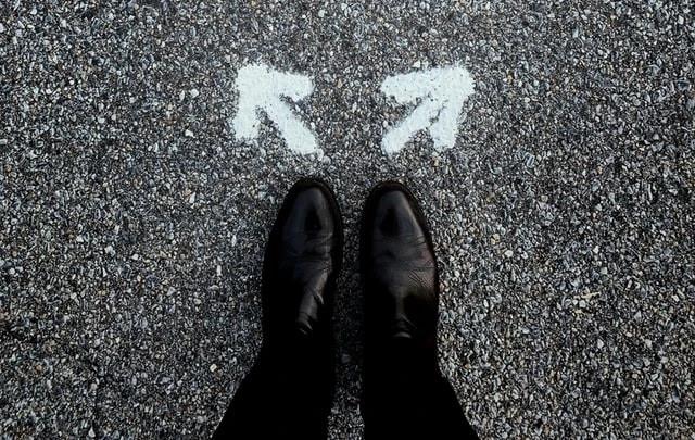 Unos pies con zapatos negros pisando un pavimento con dos flechas dibujadas