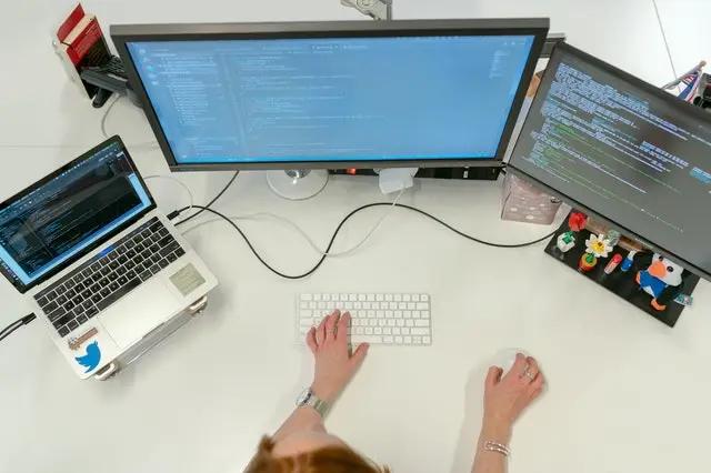 Una persona frente a dos monitores y una laptop