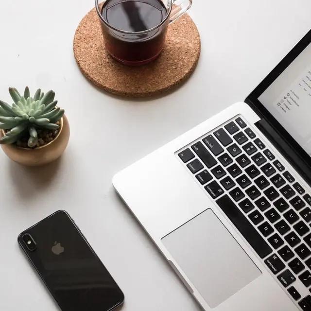 Una laptop junto a un smartphone, una planta y un café