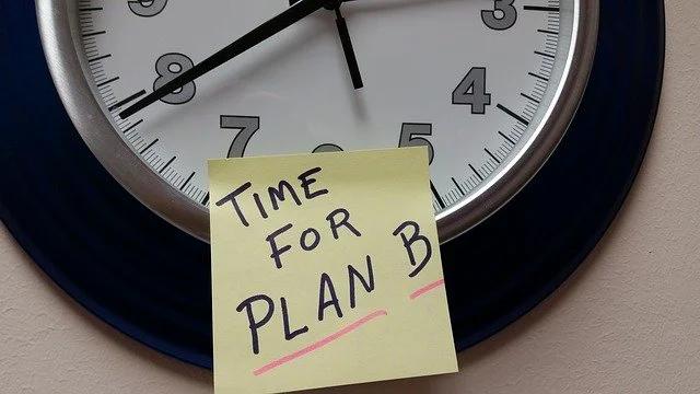 """Un reloj de pared con un post-it que dice """"Time for plan B"""""""