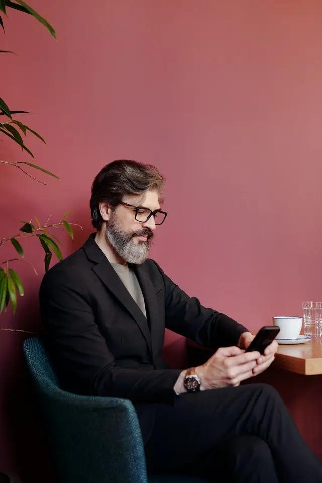 Un hombre de barba, sentado revisando su smartphone