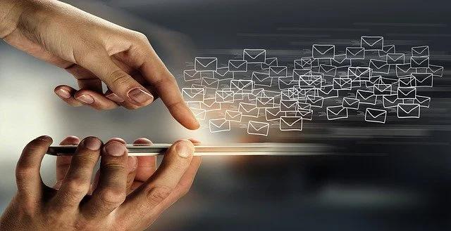 Una mano tocando una pantalla tactil encima de la cual flotan íconos de email