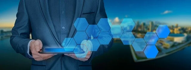 Hombre de traje sosnteniendo una tablet de la cual salen unos hexágonos azules